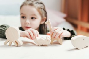 boy-girl-holding-wooden-toys